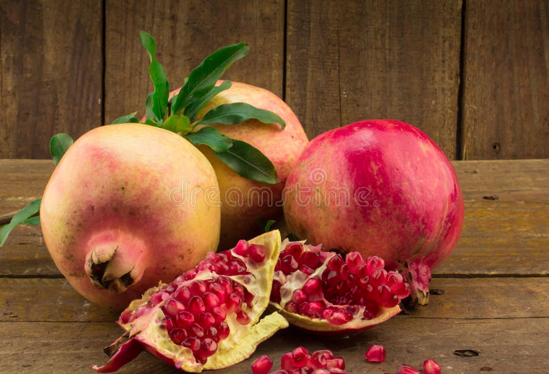 Three whole pomegranates, seeds and pieces on rustic wo royalty free stock photo