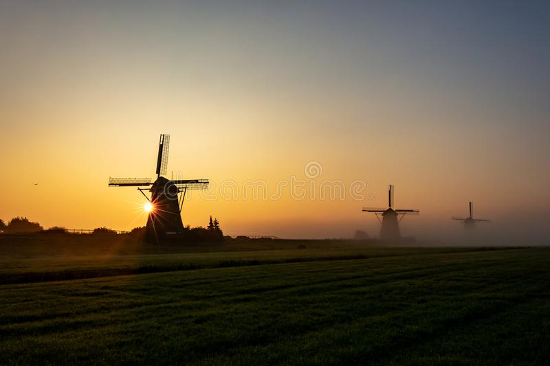 Three wind mills in the morning mist and a rising sun. Near Leidschendam, The Netherlands stock image