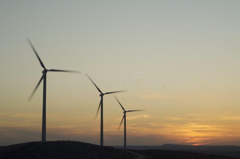 Three wind power aerogenerators skyline at dusk royalty free stock images