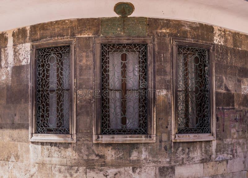 Three windows with ornamented metal lattice on a stone building. Three windows with ornamented metal lattice on a curved stone building royalty free stock photos