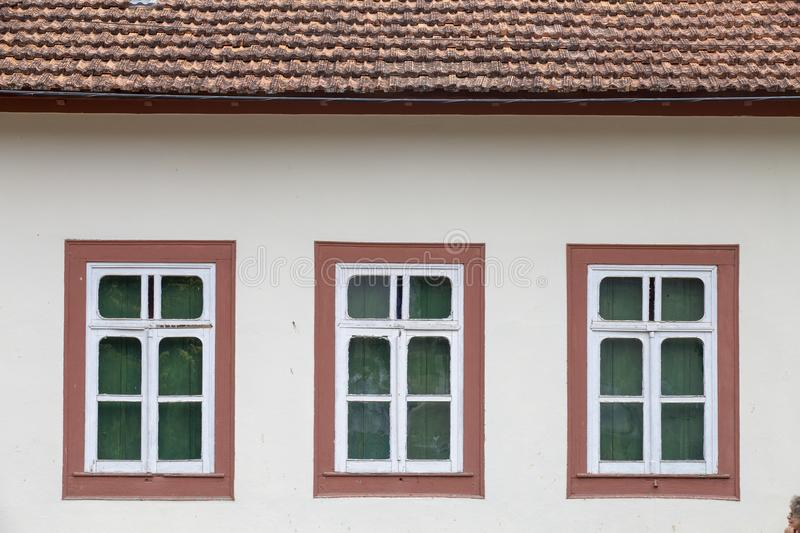 Three windows with pink frame. In symmetrical composition on the white wall stock photography