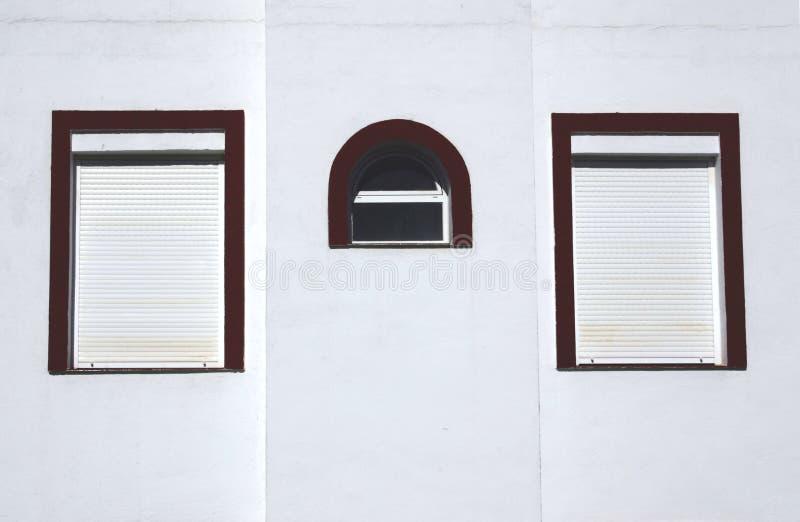 Three windows on a wall stock photo
