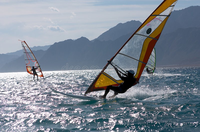 Three windsurfers. In patches of light of a sunlight stock photos