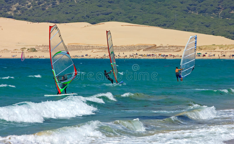 Three windsurfers on sandy Tarifa beach in southern Spain royalty free stock images