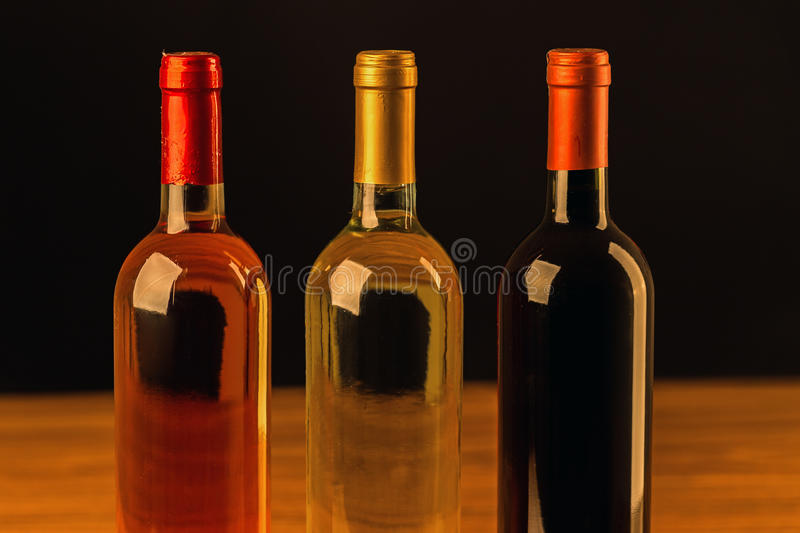 Three wine bottles on wooden table and black background stock images