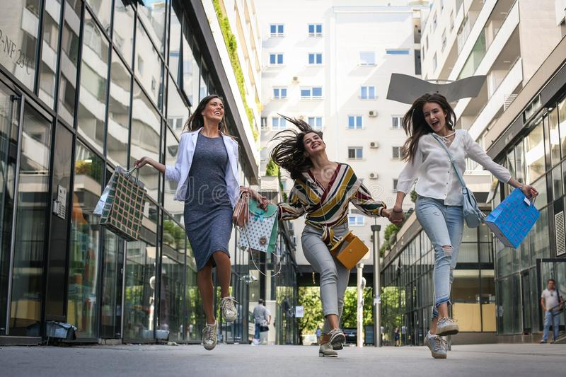 Three woman walking happy and satisfied city street after shopping. stock images