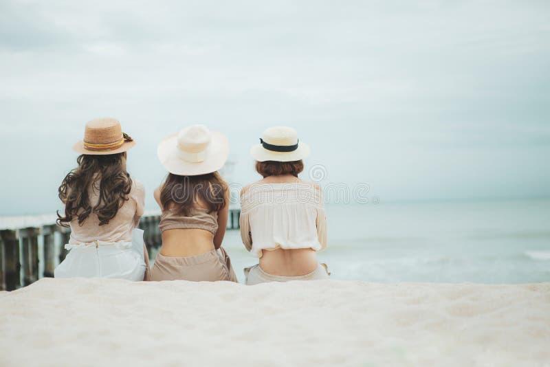 Three woman wearing straw hat  sitting on vacation sea beach stock image