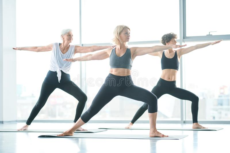 Stretching practice. Three women in activewear outstretching their arms while standing on mats during yoga exercise in gym royalty free stock photography