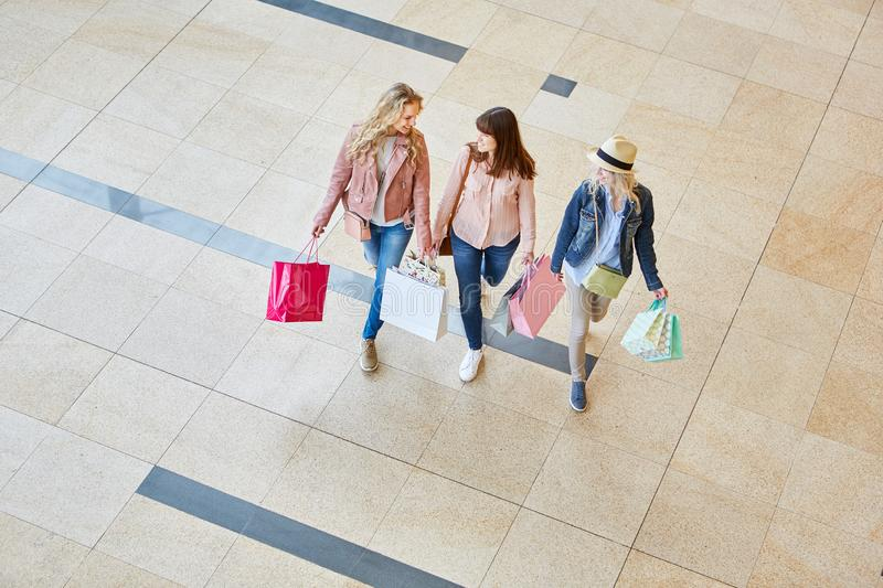 Three women as friends in shopping mall stock image