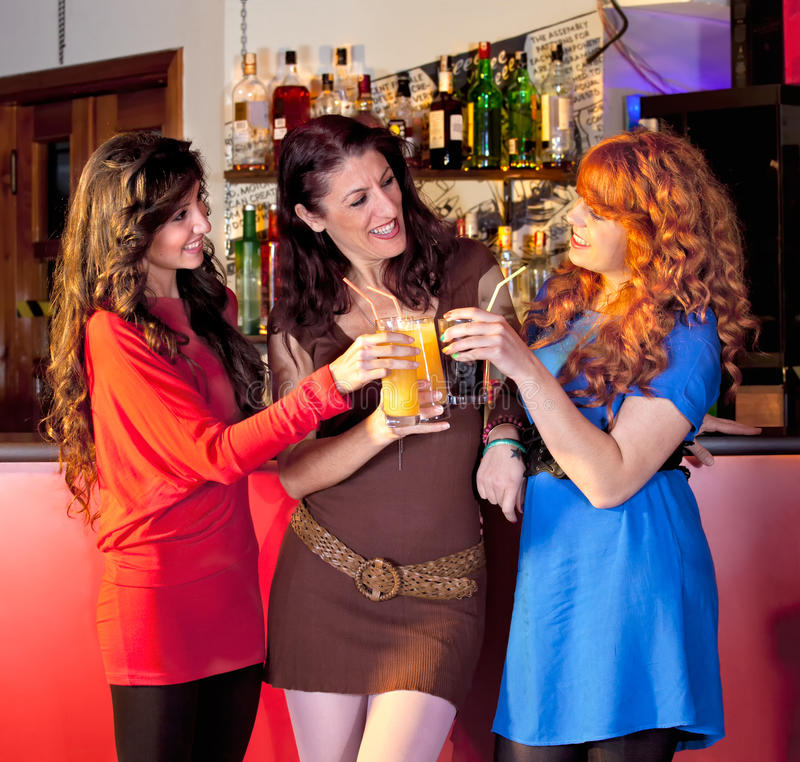 Three Women In A Bar Holding Glasses. Stock Images