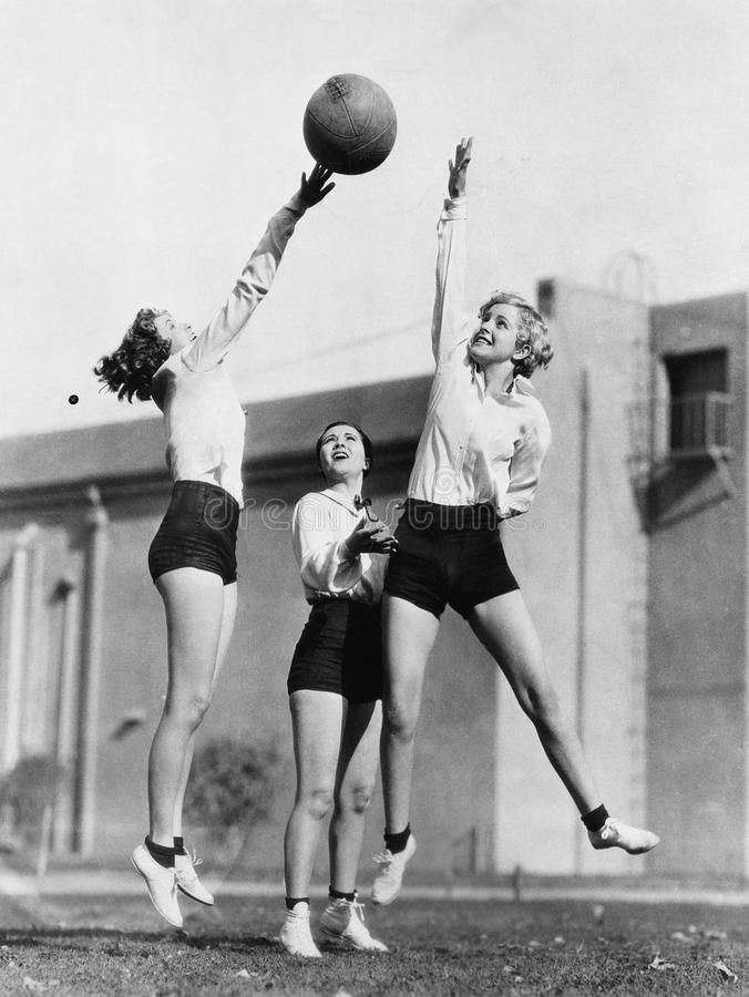 Three women with basketball in the air stock photography
