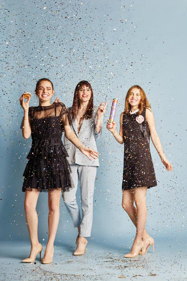 Three women celebrate the holiday having fun laughing and eating cakes under the flying confetti. Girls posing and smiling on blue royalty free stock photos