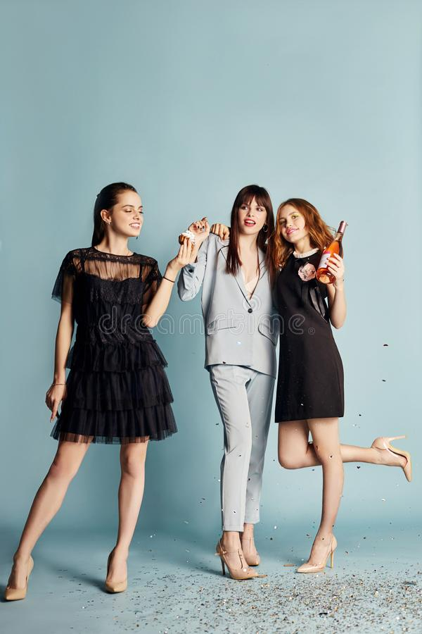 Three women celebrate the holiday having fun laughing and eating cakes under the flying confetti. Girls posing and smiling on blue royalty free stock image