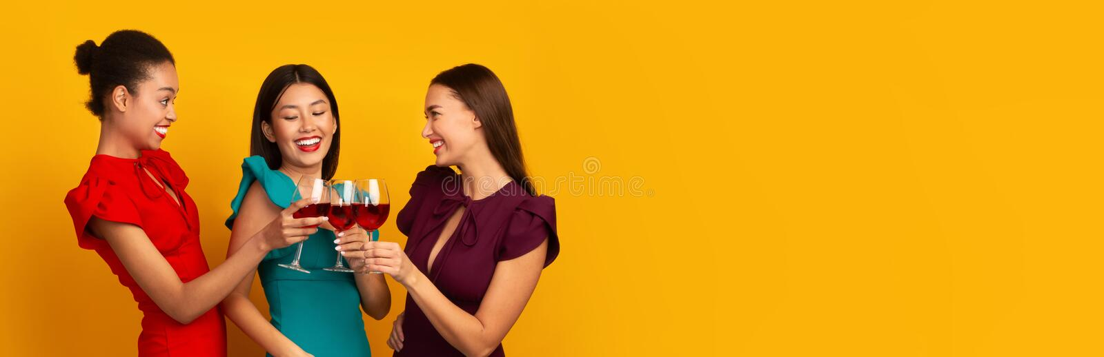 Three Women Clinking Red Wine Glasses Laughing Standing, Yellow Background royalty free stock photography