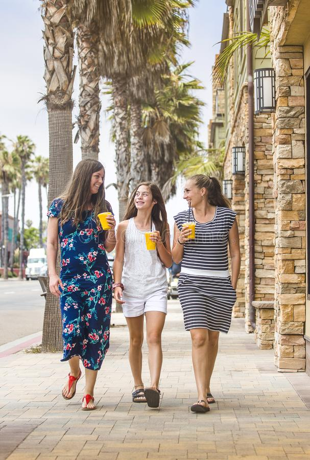 Three women drinking fruit smoothies while walking down street. Three women drinking fruit smoothies while walking and talking outdoors down a commercial street stock photo
