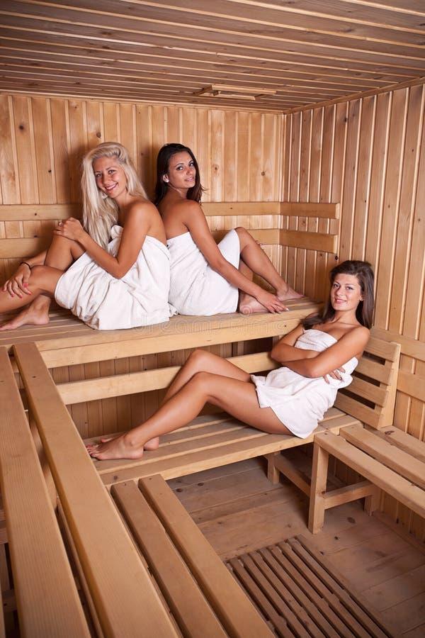 Three women enjoying a hot sauna royalty free stock image