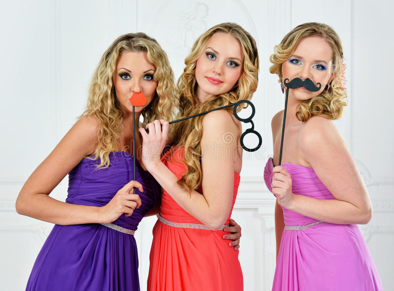 Three women in evening gown with masks. royalty free stock image