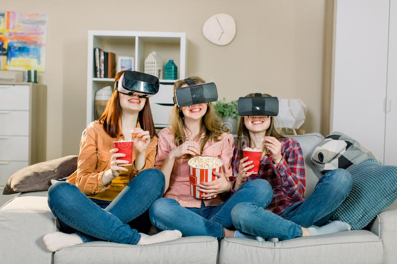 Three women excited using 3d goggles watching virtual reality vision enjoying cyber fun experience in vr simulation stock images