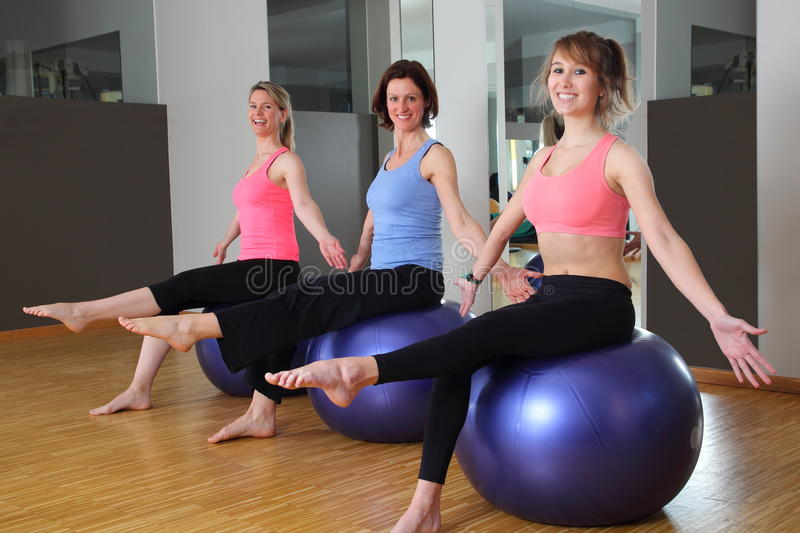 Three women on exercise balls in a gym hands legs up. Three women on exercise balls in a gym with hands legs up stock images