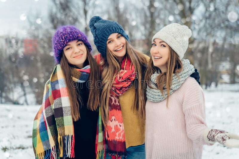 Three women friends outdoors in knitted hats having fun on a snowy cold weather. Group of young female friends outdoors royalty free stock photography