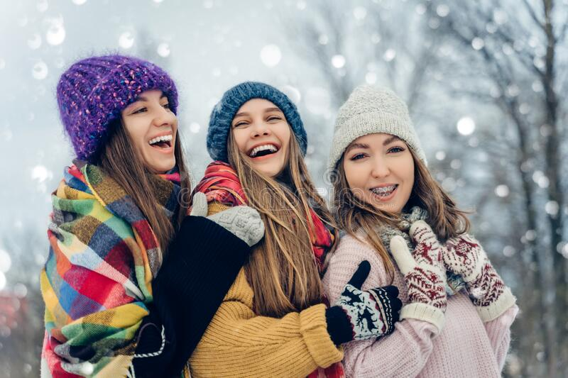 Three women friends outdoors in knitted hats having fun on a snowy cold weather. Group of young female friends outdoors royalty free stock photos