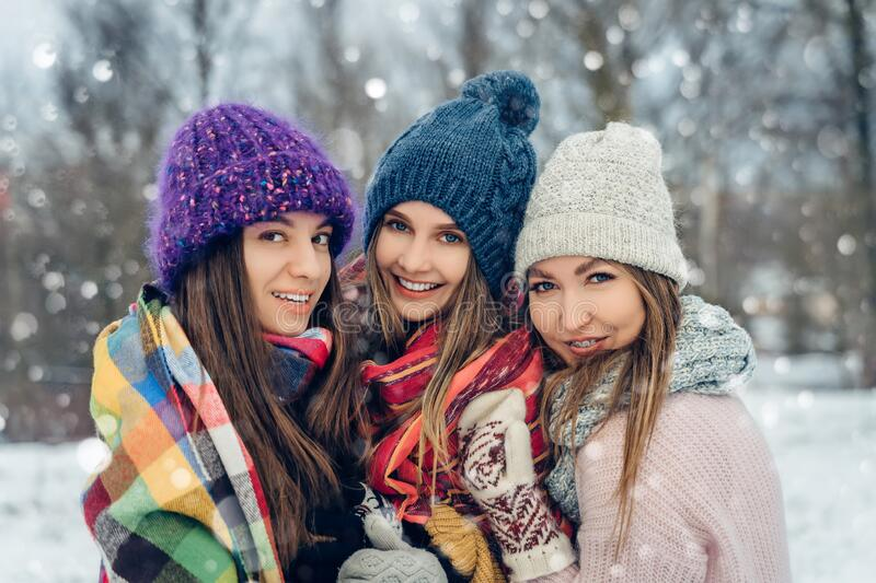 Three women friends outdoors in knitted hats having fun on a snowy cold weather. Group of young female friends outdoors royalty free stock images