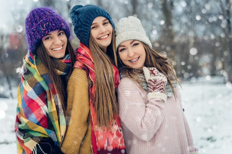Three women friends outdoors in knitted hats having fun on a snowy cold weather. Group of young female friends outdoors stock image