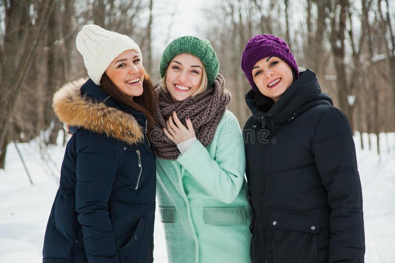 Three women friends outdoors in knitted hats on a snowy cold winter weather. royalty free stock images