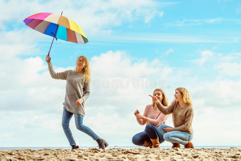 Women holding umbrella having fun with friends stock image