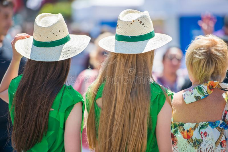 Three women in green gress. With long blond hair and crowd of people stock image