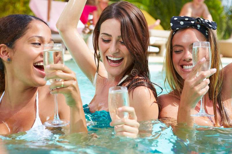 Three Women Having Party In Swimming Pool Drinking Champagne royalty free stock image