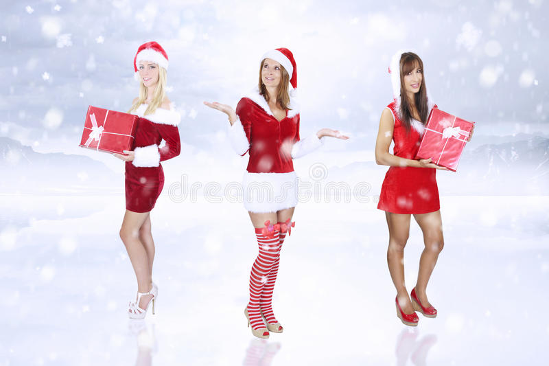 Three women holding a Christmas present. Over a snowy background stock images