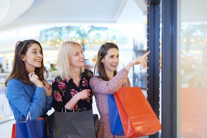 Three women looking at window display stock image