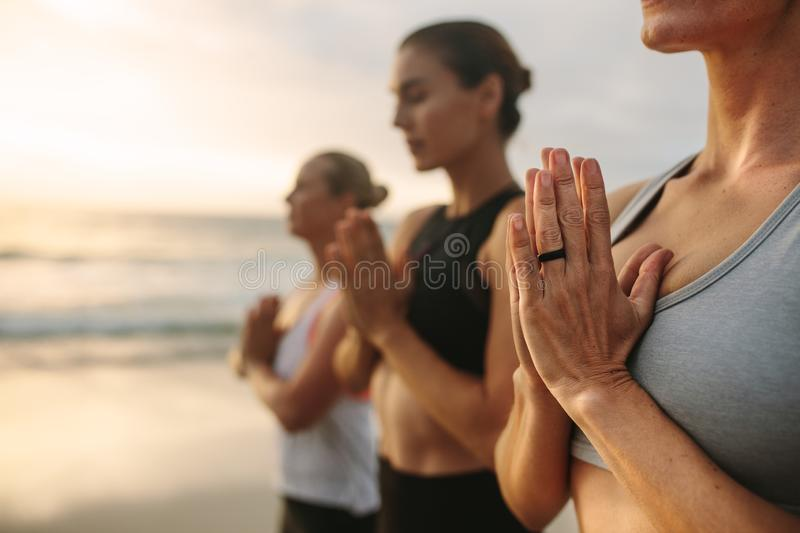 Three women meditating at the beach. Women practicing yoga on the beach early in the morning. Fitness women standing at the beach meditating with joined palms stock photography