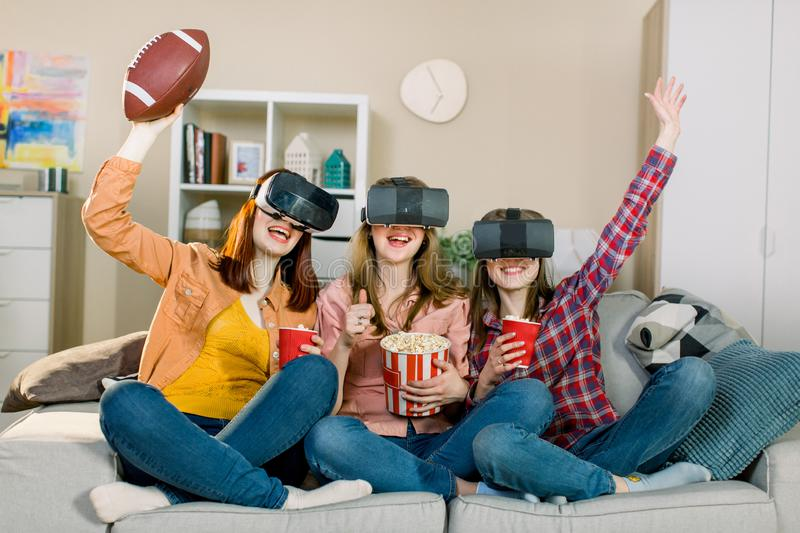 Three women in modern virtual reality headsets having expirience in watching football match at home. Girls in vr glasses stock photography