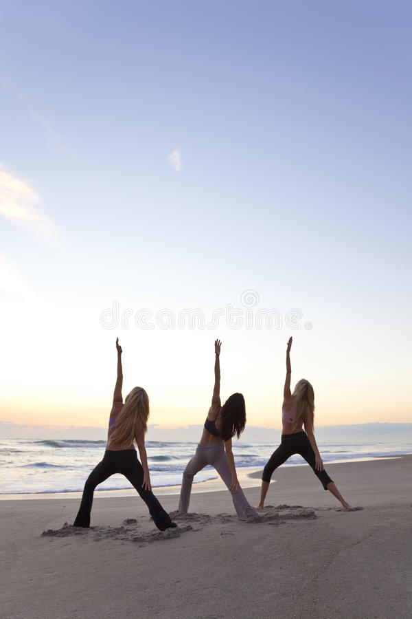 Three Women Practicing Yoga on Beach At Sunrise. Three young women in a warrior position practicing yoga on a beach at sunrise or sunset royalty free stock photography