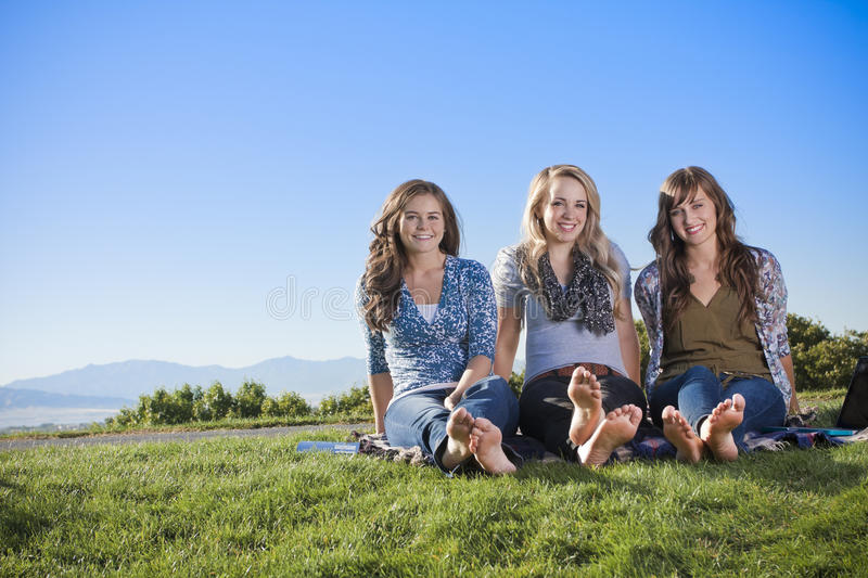 Three women relaxing in the outdoors. Three young attractive women relaxing on a blanket at the park and enjoying the outdoors. Lots of copy space stock image
