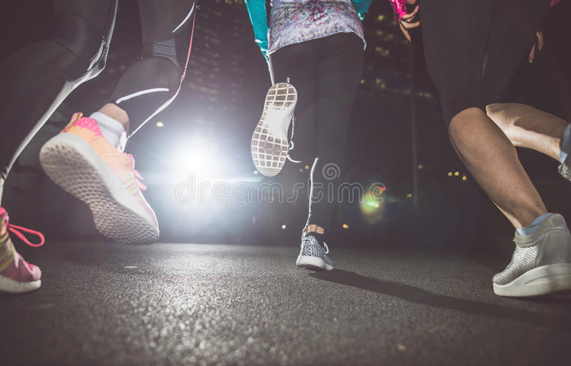 Three women running in the night royalty free stock images