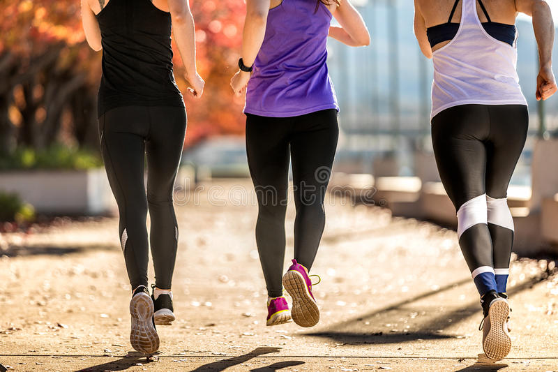 Three women running on street royalty free stock photo