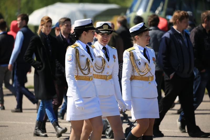 Three women in Russian white military uniform are walking among people stock photos