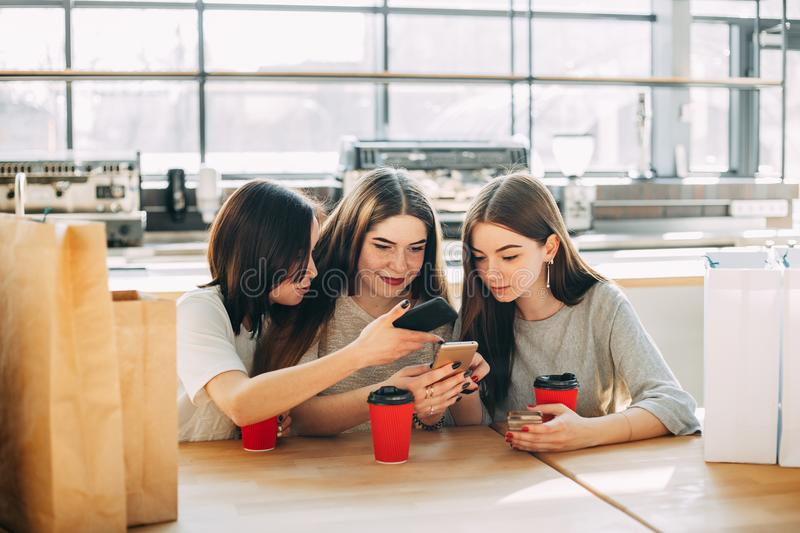 Three women shopping online sitting at cafe. Three friends shopping online sitting at cafe. Group of women sit at the table with shopping bags using smart phone royalty free stock photo