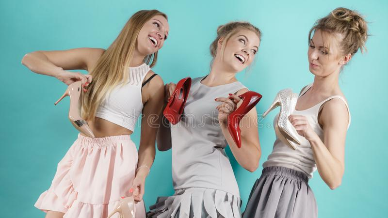 Three women showing high heels shoes stock photography