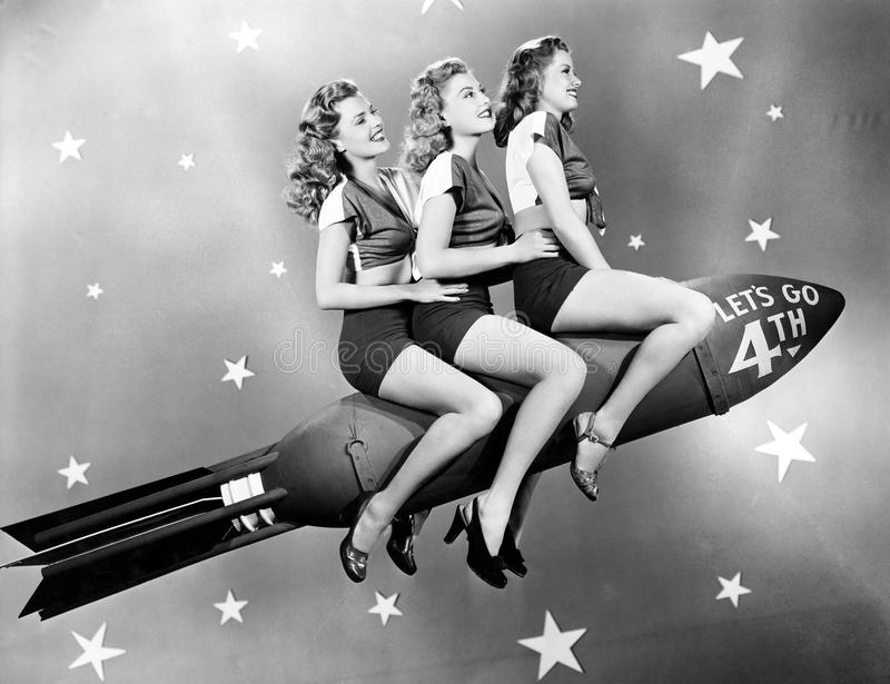 Three women sitting on a rocket stock photography