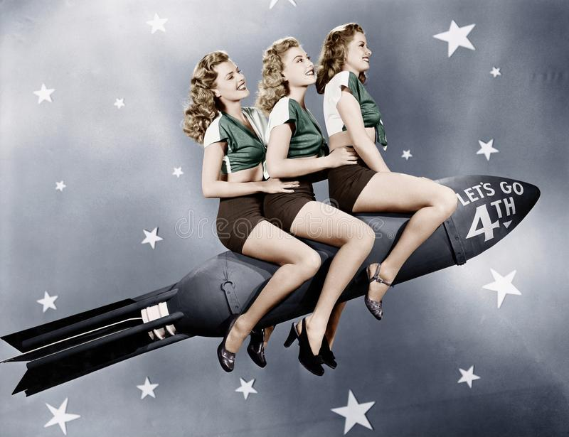 Three women sitting on a rocket royalty free stock photo