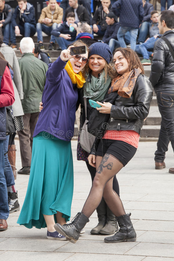 Three women smiling doing a selfie with phone. Three smiling girls are doing a selfie with their phone. They are three tourists visiting Barcelona, Spain. Behind royalty free stock photography