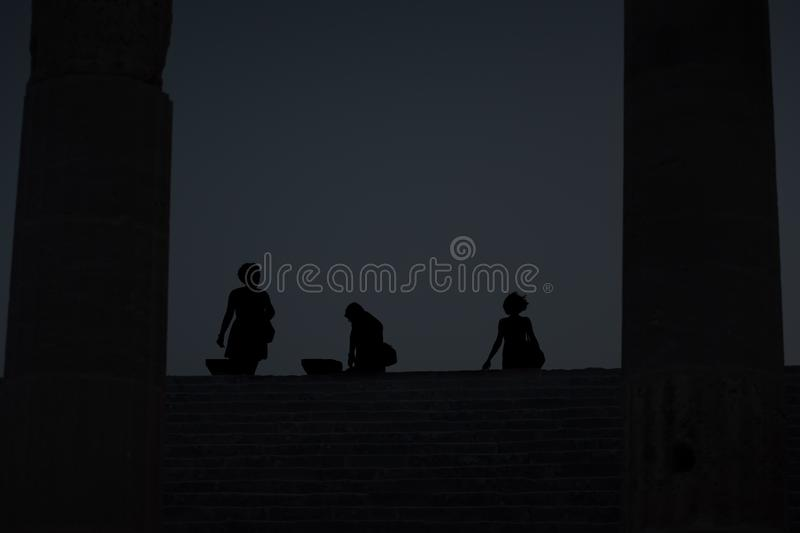 Three women on Staircase of Propylaea after sunset on Acropolis. Of Lindos Rhodes, Greece stock photography