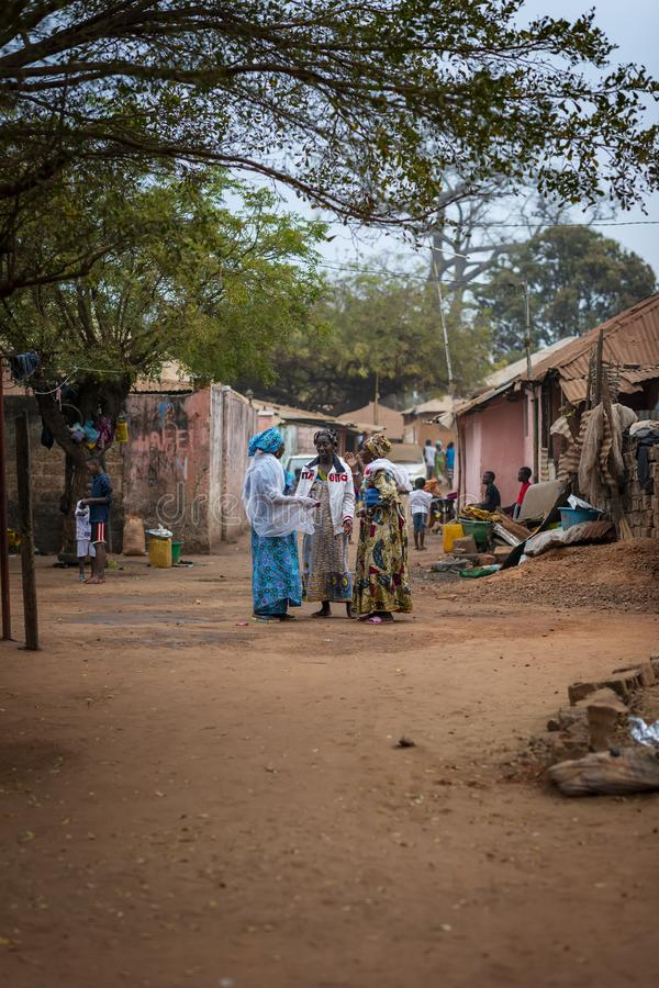 Three women talking on a street at the Missira neighborhood, in the city of Bissau stock photo