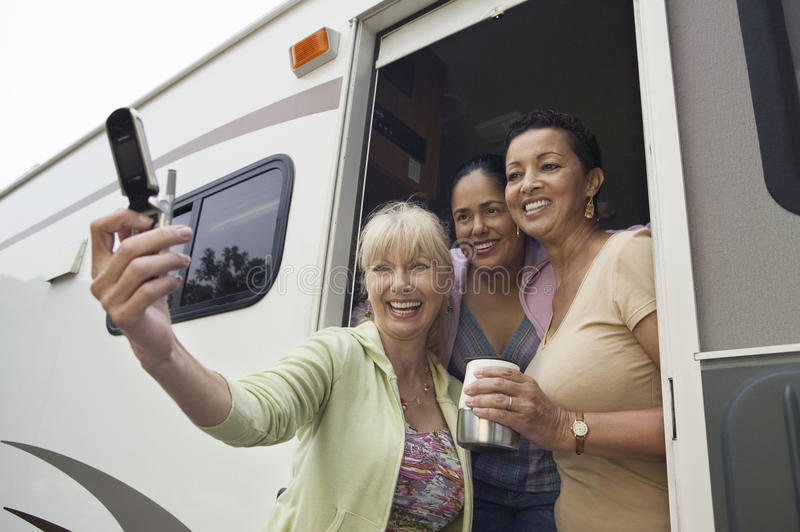 Download Three Women Using Camera Phone In Motor Home Stock Image - Image: 30839595