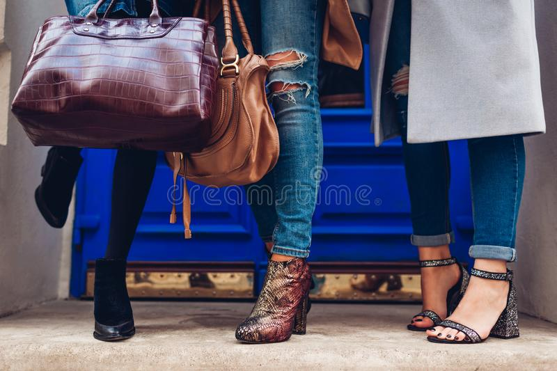 Three women wearing stylish shoes and accessories outdoors. Beauty fashion concept. Ladies holding female handbags stock photo
