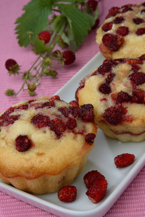 Three wood strawberry muffins on plate royalty free stock photography